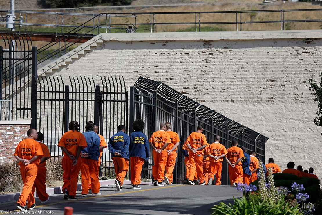 A row of general population inmates, handcuffed and in orange jumpsuits, walk in a line at San Quentin State Prison.