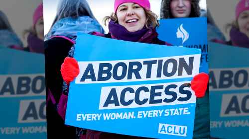 Woman holding abortion access sign at a rally