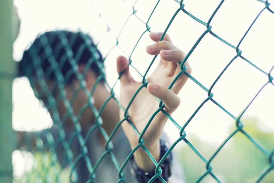 Child leaning on chainlink fence
