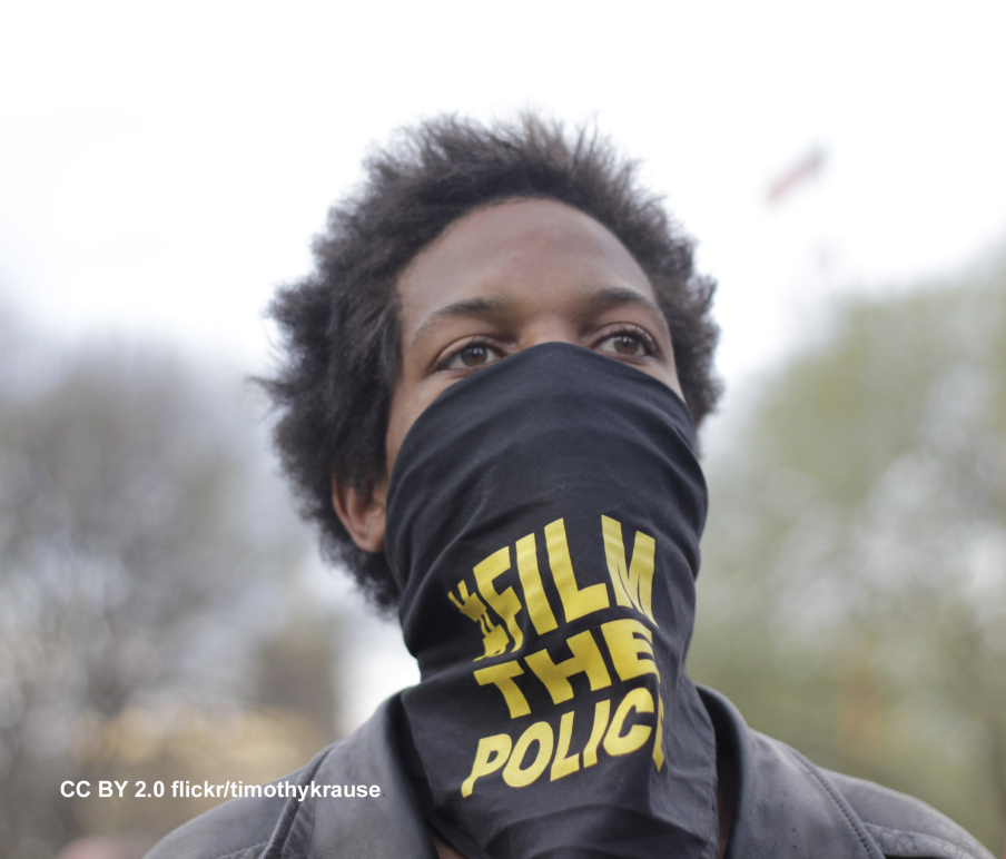 Young Black man with black bandana covering his mouth. Bandana says FILM THE POLICE in yellow letters.