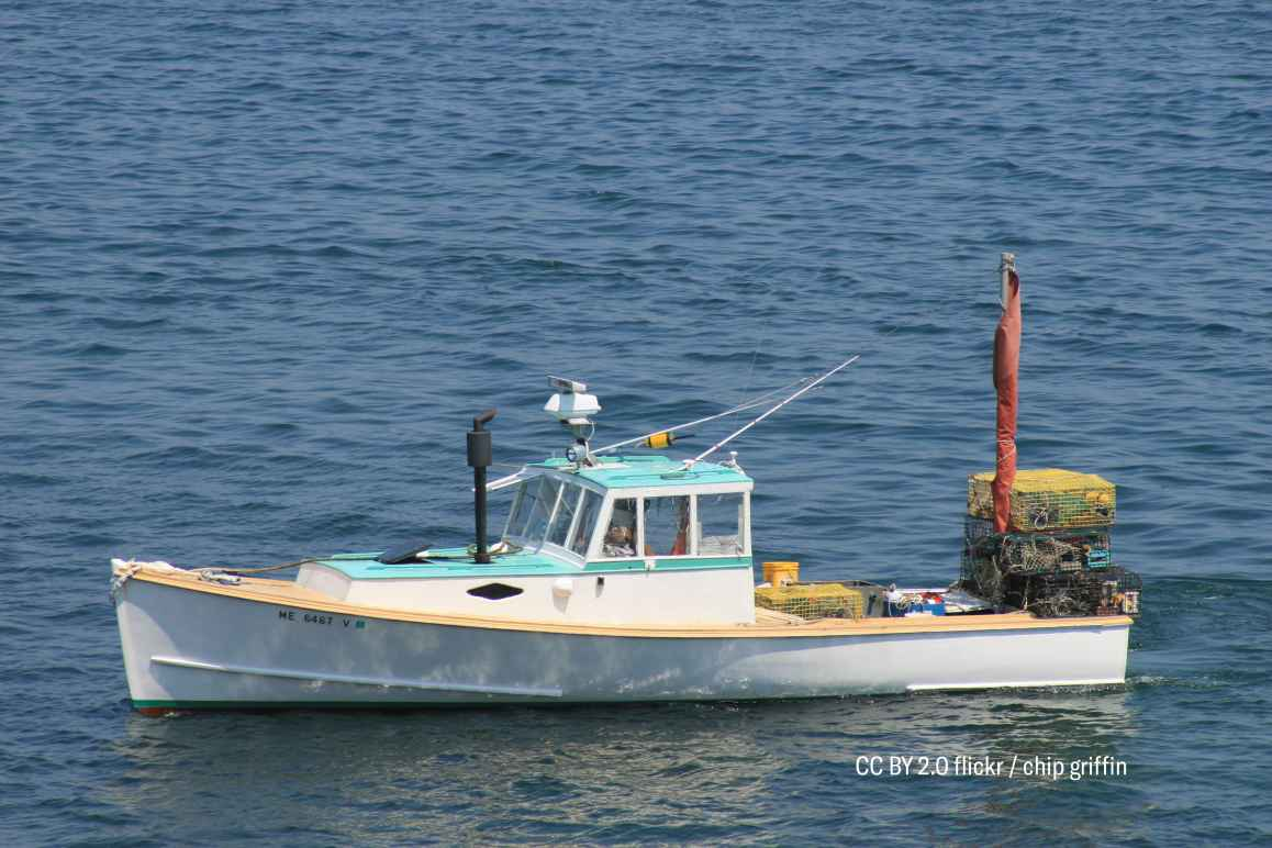 white lobster boat with traps in Maine harbor