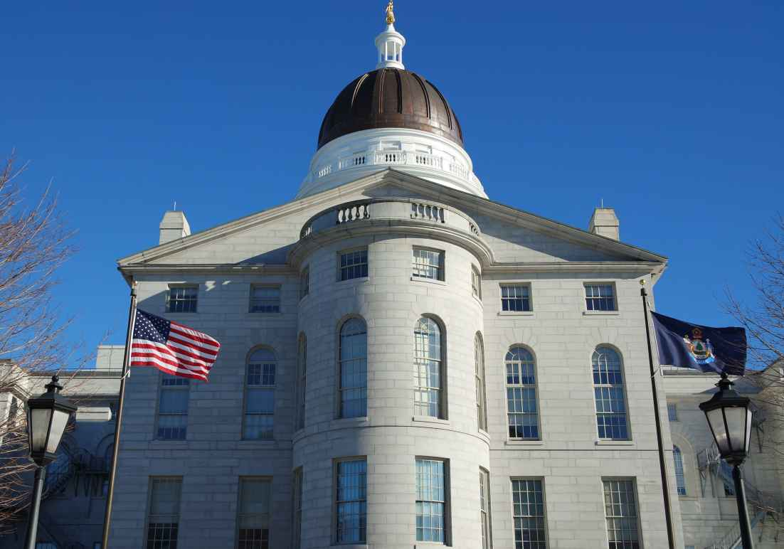Maine Capitol building with American flag