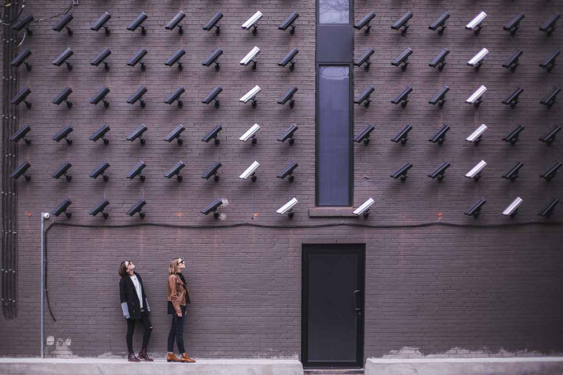 Two women looking up at a wall covered in security cameras