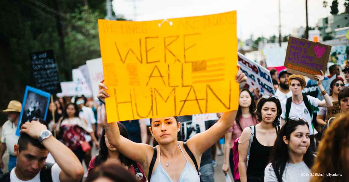 "Immigrants' rights rally with woman holding sign that reads ""We're All Human"""