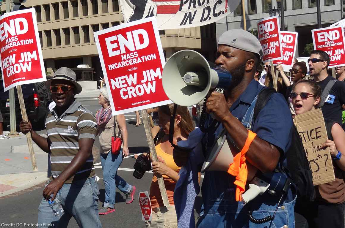 Demonstrators carry signs advocating an end to mass incarceration