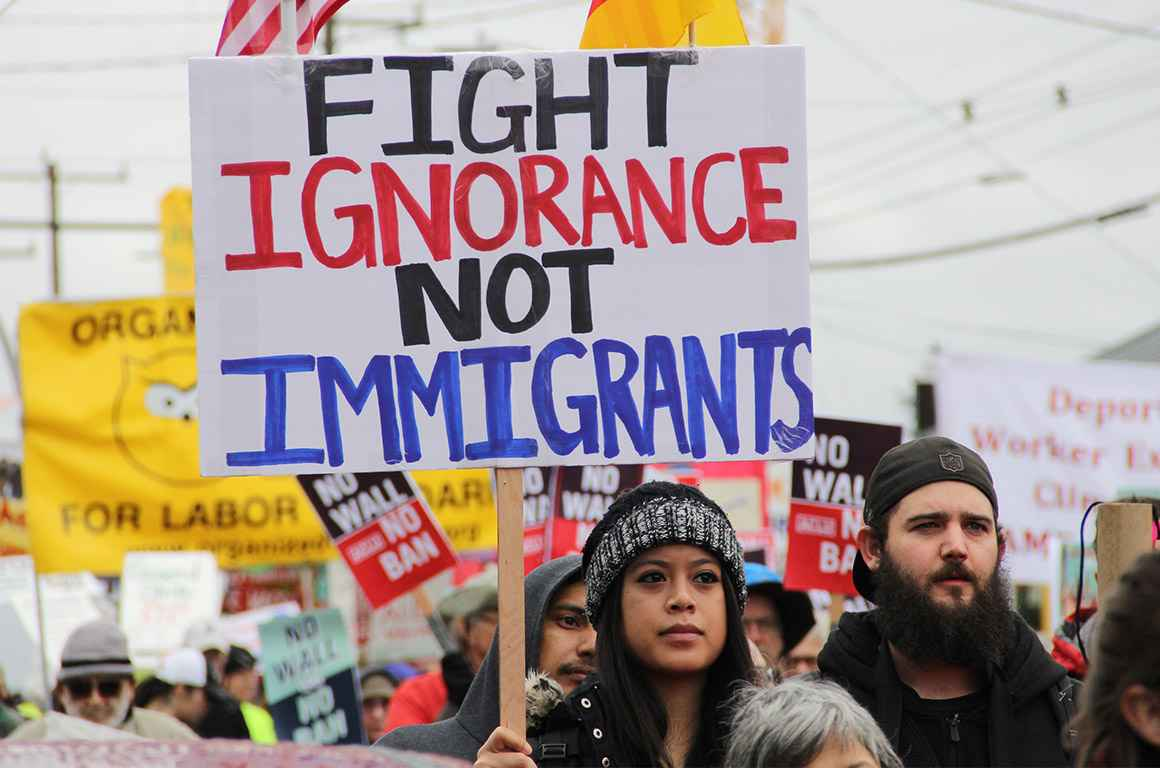 """A protester holding a sign with the text """"fight ignorance not immigrants"""""""