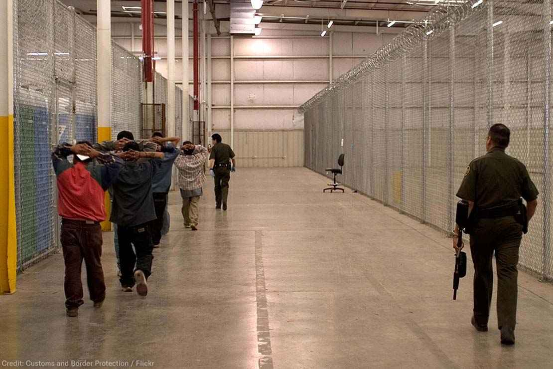 Immigrant detainees walk down a hall escorted by heavily armed CBP officers.
