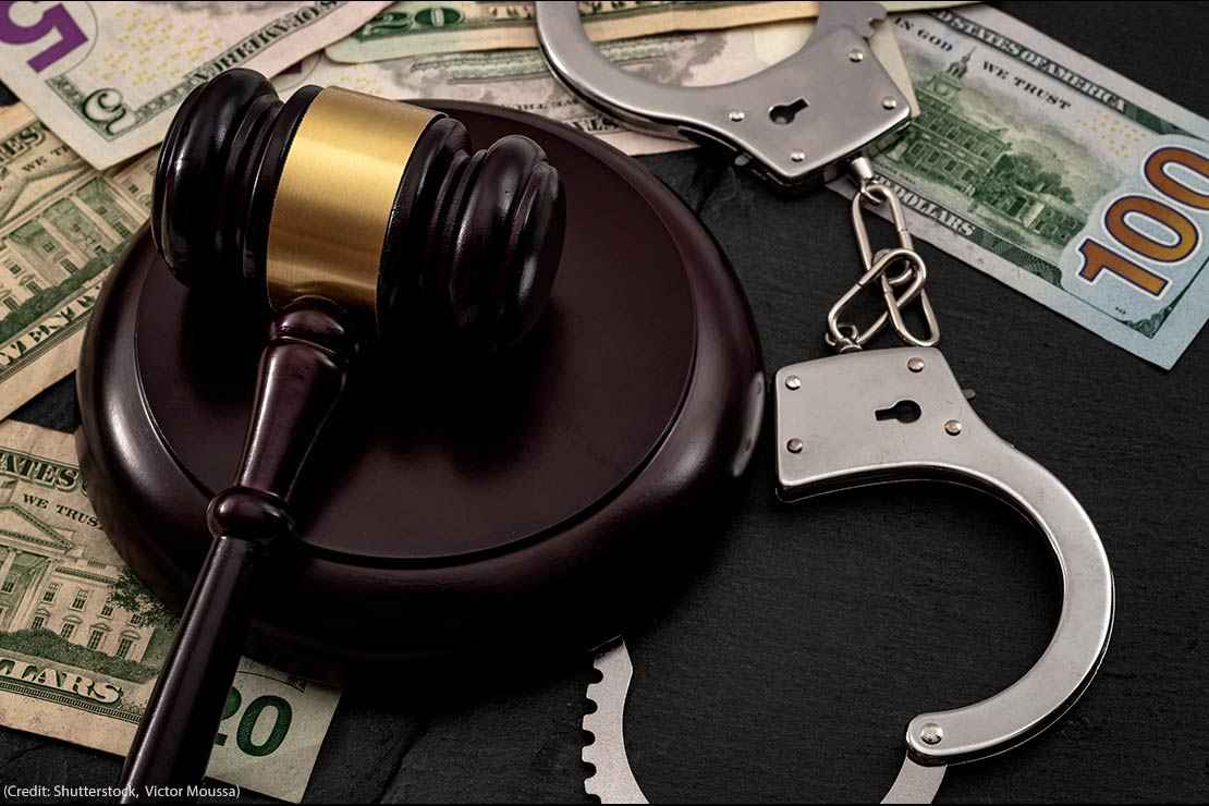 A gavel and a pair of handcuffs on a pile of money.