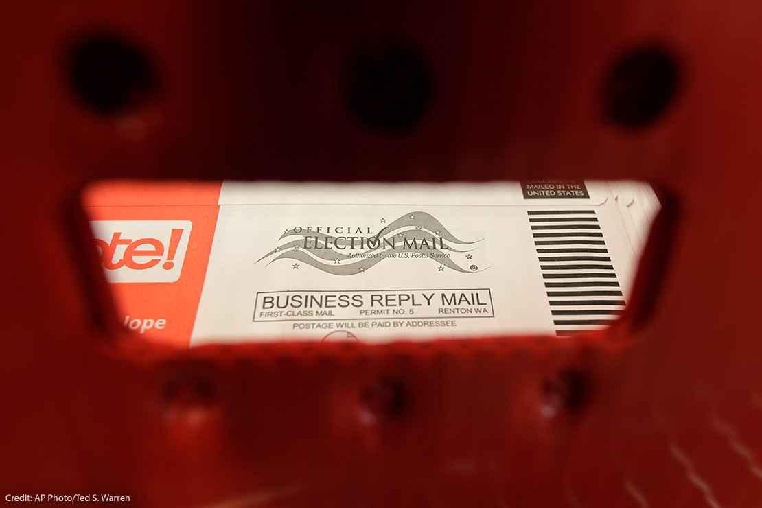 Absentee ballots are seen through a mailbin