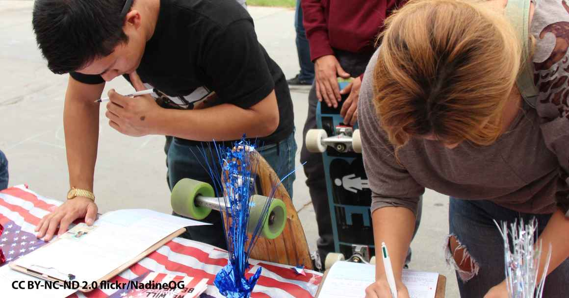 Two students leaning over a table filling out voter registration information