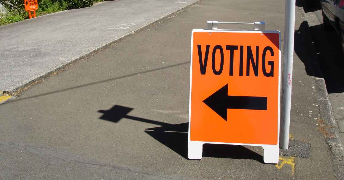 Sign on the sidewalk directing people to a polling location.